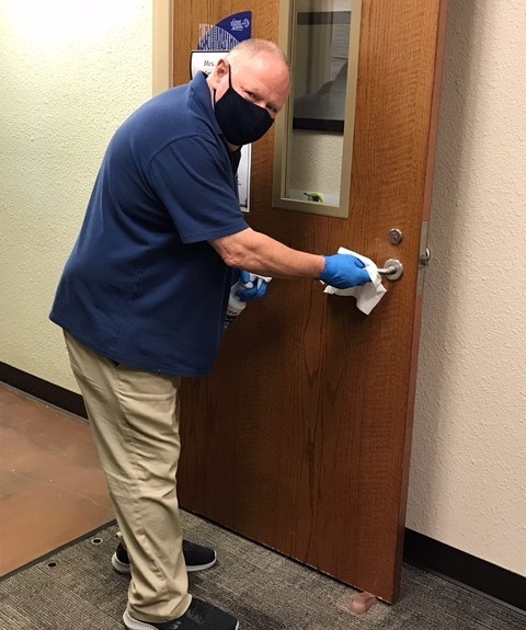 custodian cleaning door handle